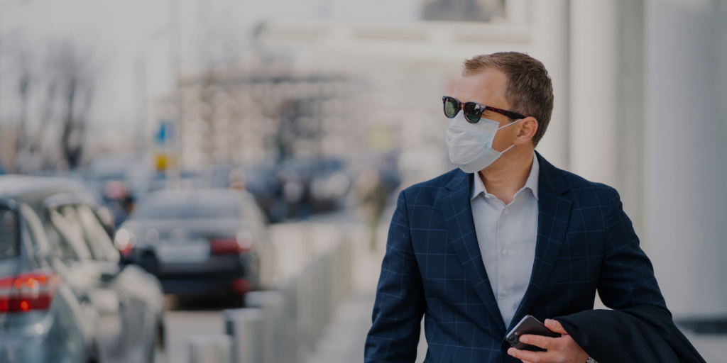 A man walking in the city with mask due to COVID19